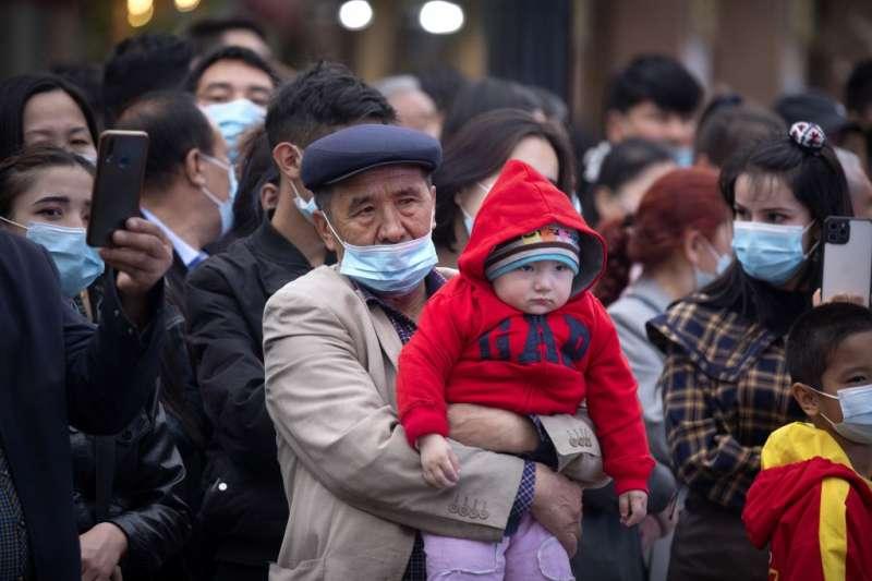 新疆維吾爾自治區的烏魯木齊,一位男性抱著孩子在街頭觀看舞蹈表演。(美聯社)
