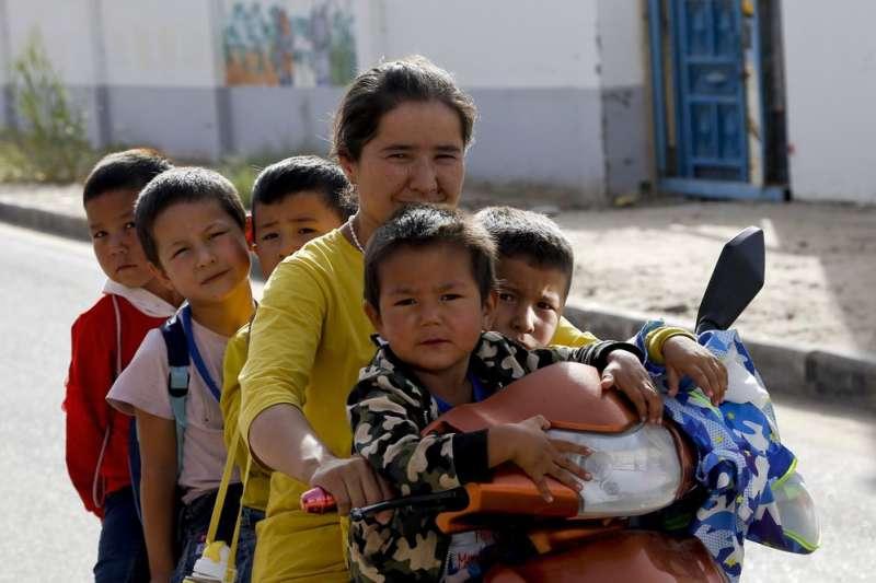 2018年9月,中國新疆和田市,一名維吾爾族婦女騎著摩拖車載孩子(美聯社)