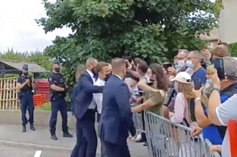 法國總統馬克宏走訪各城市,探視新冠疫情後生活狀況。8日與民眾握手致意時,遭一名男子甩巴掌。(AP)