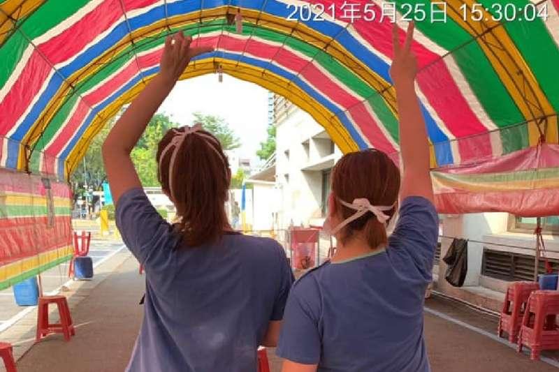 高雄市長陳其邁在臉書po一張兩名護士在篩檢站剛忙完,汗流浹背向前招手的照片,好像在彩色隧道中迎向光明,是最美麗的背影。(圖/翻攝陳其邁臉書)