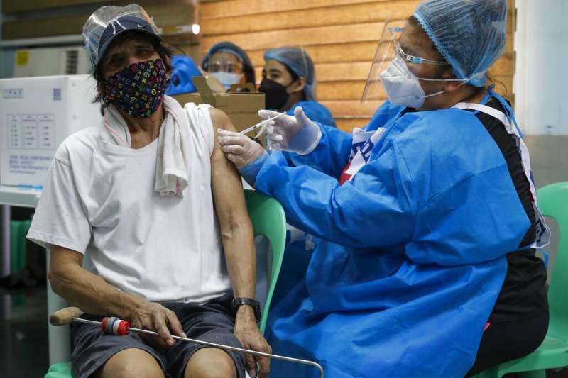 菲律賓的醫護人員正在為港口工人施打中國的科興疫苗。(美聯社)