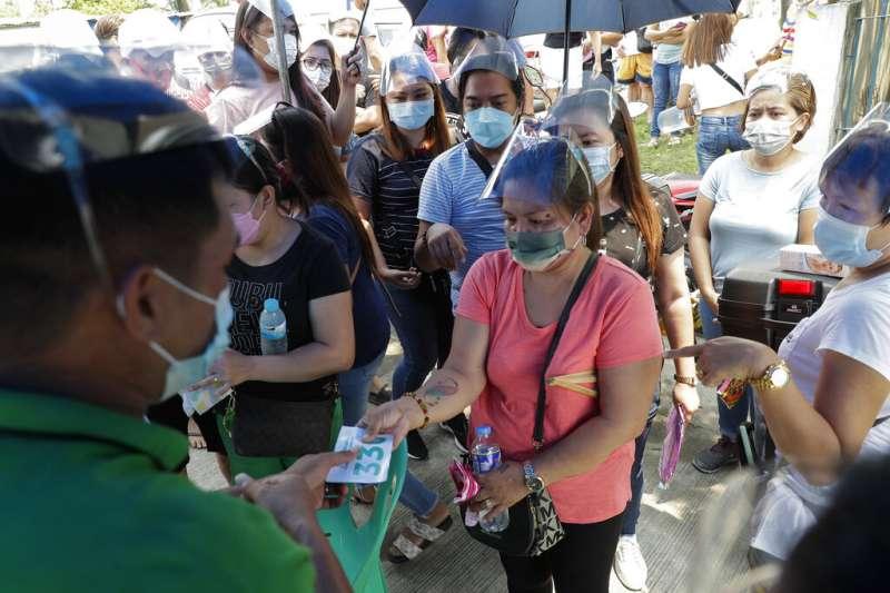 菲律賓的民眾正在排隊領取號碼牌,準備接種新冠疫苗。(美聯社)