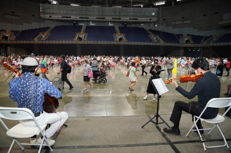 高雄市政府邀請音樂家方元之間樂團團長蔡世宏的吉他演奏,搭配高雄市交響樂團小提琴家蔡宗言合奏,演出大家耳熟能詳的精選曲目,與現場醫護、民眾一起沉浸在療癒的音樂聲中。(圖/高雄市政府提供)