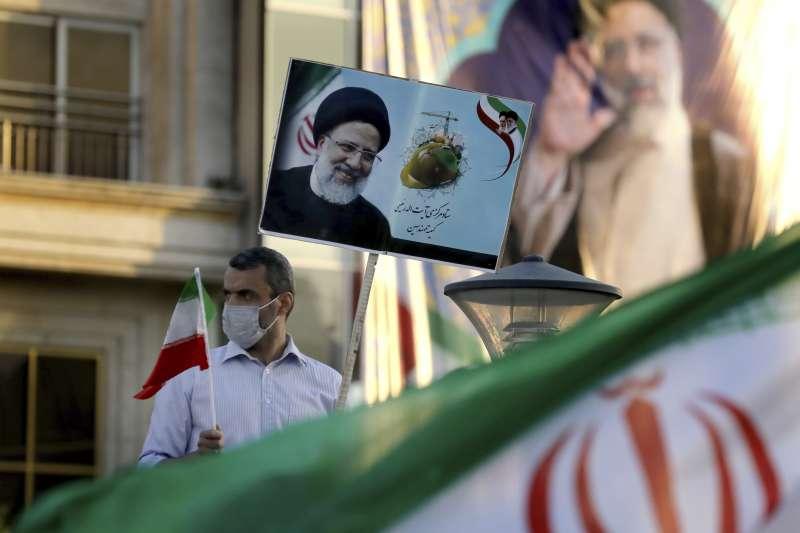 伊朗總統大選:司法總監萊希的支持者高舉他的照片和伊朗國旗(AP)