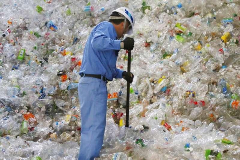 2019年6月,日本東京一間塑膠回收公司的員工正在處理塑膠瓶(美聯社)