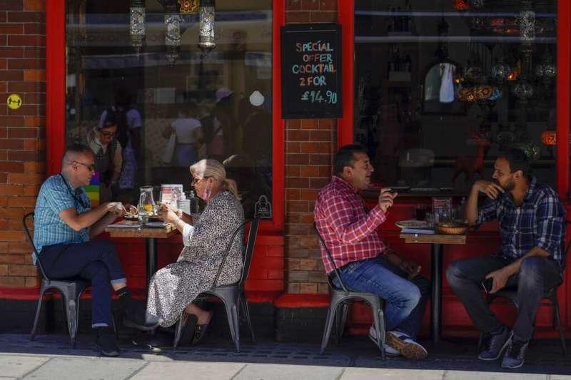 英國封城期間在室外用餐的民眾。(美聯社)