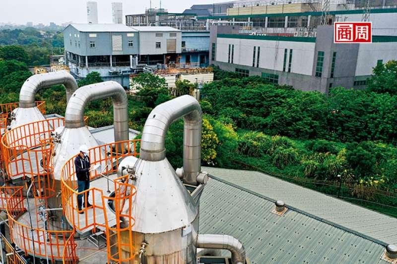 圖中工作人員所在地,是友達為擺放零排放設備,在廠外找到的一片800多坪畸零地;而圖後方的廠房,就是友達龍潭廠。(圖/程思迪攝)