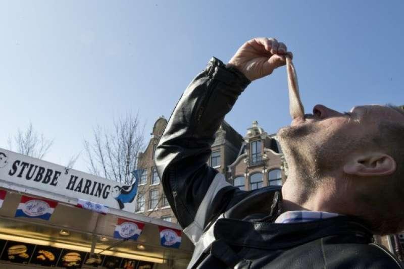 荷蘭流行抬頭張口生吞鯡魚的吃法(AP)