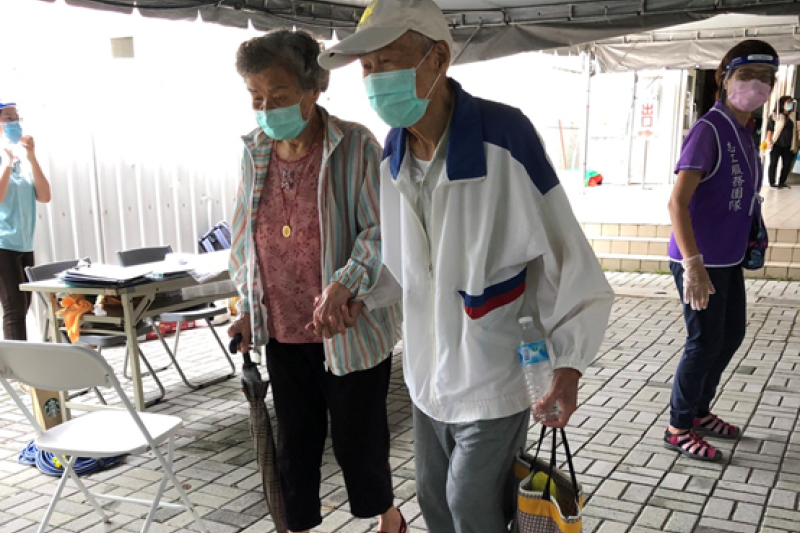 阿公牽著行動不方便的老伴一同至前鎮區福誠高中接種站打疫苗。(圖/高雄市政府提供)