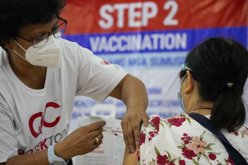 目前已累計136萬人確診感染新冠病毒的菲律賓,昆松市一位民眾正在接種新冠疫苗。。(美聯社)