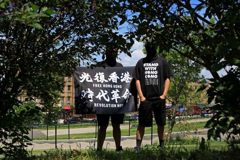 手拿標語的Ray(左)和Tommy本月在紐約,他們正在美國申請庇護。 (圖/YANA PASKOVA FOR THE WALL STREET JOURNAL)