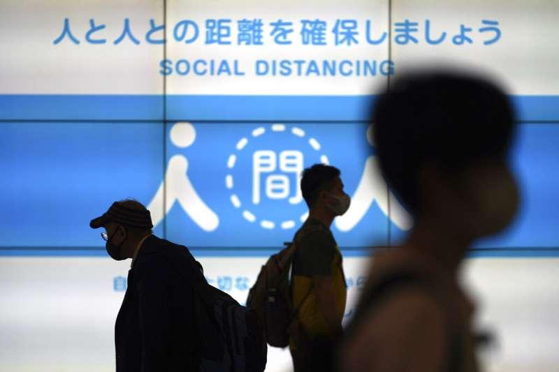 東京街頭宣導保持社交距離的巨幅廣告。(美聯社)
