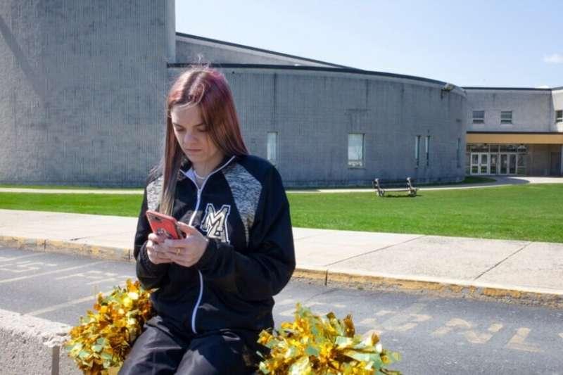 在這張由美國公民自由聯盟(ACLU)提供的照片中,布蘭迪 · 利維坐在她曾就讀的賓州馬哈諾伊地區高中外。(美國之音)