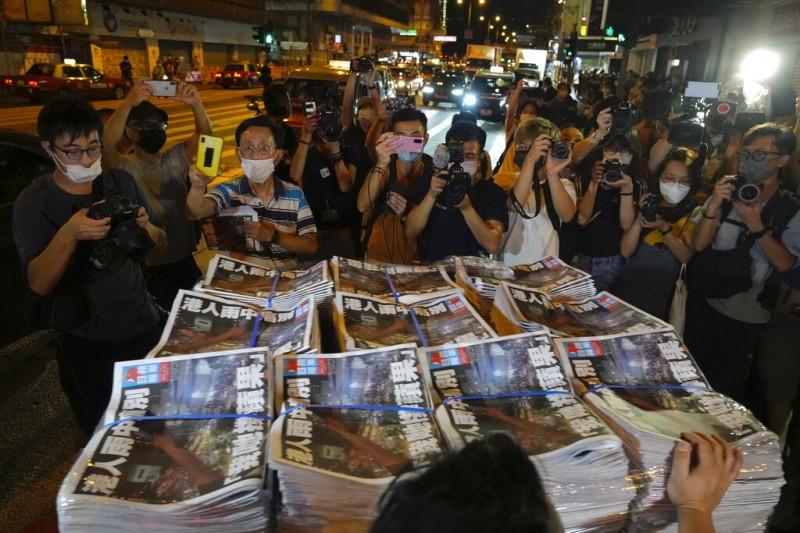 2021年6月24日凌晨,最後一期香港《蘋果日報》一被送到報攤,已經有無數媒體與市民在現場等候。最後一夜,員工聚集在天台與窗口用手機燈光與照亮黑暗的夜空。(美聯社)