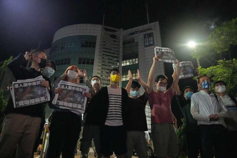 2021年6月24日凌晨,香港《蘋果日報》的員工走出位於將軍澳的總部大樓,手持最後一期報紙向市民鞠躬致謝。(美聯社)