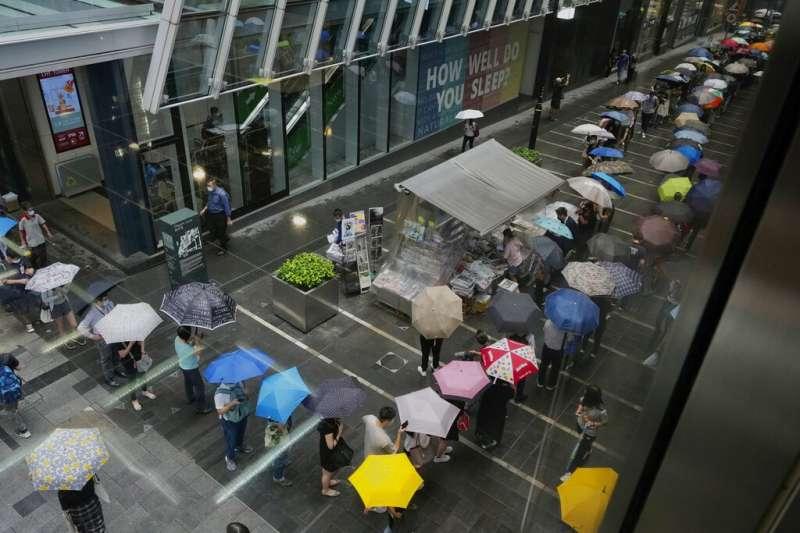 2021年6月24日,許多香港市民排隊搶購最後一期《蘋果日報》。(美聯社)