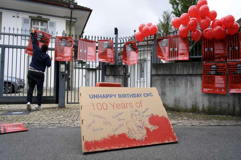 中共紀念創黨百年當天,幾位流亡藏人在瑞士伯恩的中國大使館外掛起抗議標語。(美聯社)