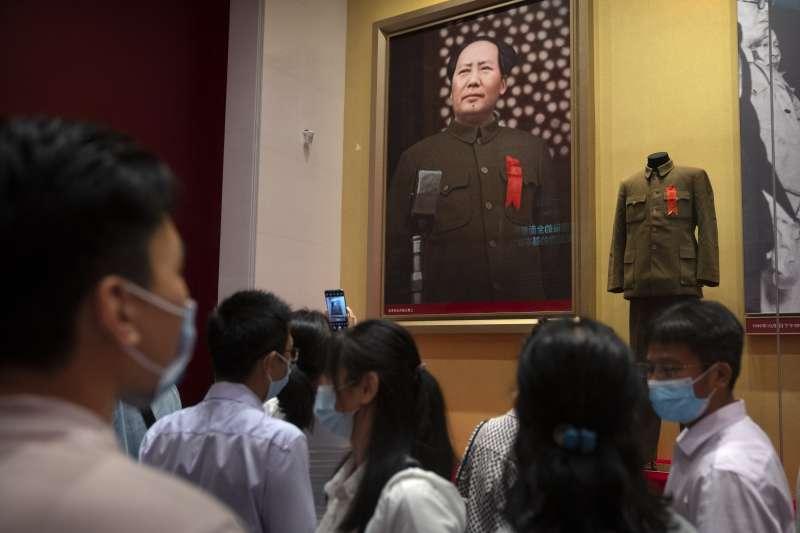遊客在北京新開幕的中共紀念館觀看毛澤東的照片,他當時正在天安門的城樓上宣布新中國的成立。(美聯社)