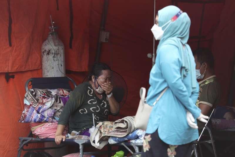 6月28日,印尼爪哇島勿加泗市一家醫院搭建的臨時帳篷內,病患正坐在裡面休息(美聯社)