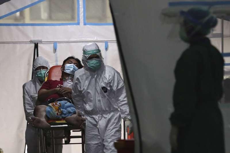 6月24日,印尼雅加達的珍加連地區綜合醫院,醫護人員用擔架將一名新冠病患抬離緊急搭建的帳篷(美聯社)