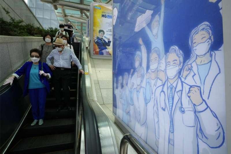 首爾地鐵站的海報繪製著醫護人員正在為民眾加油。(美聯社)