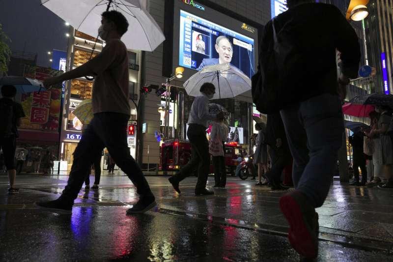 東京鬧區街頭的大螢幕上,正在播放菅義偉宣布東京將在7月12日進入第四波緊急事態的記者會。(美聯社)