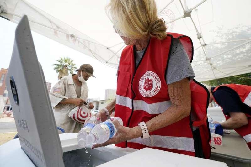 補給站的志工們在分發冰水給不敵高溫的民眾(取自AP)