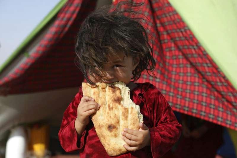 2021年7月8日,一個阿富汗小女孩在北部難民營裡吃著麵包。美聯社稱,她的家人因為阿富汗爆發內戰流離失所,只得離家逃往北方。因為阿富汗北部有與美國結盟的軍閥據點。(美聯社)