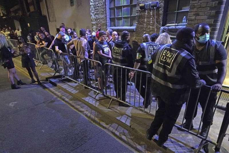 7月18日深夜,英國倫敦民眾排隊等待進入酒吧(美聯社)