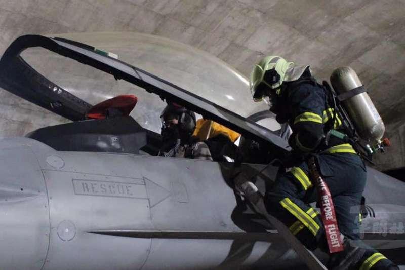 身揹氣瓶、著全套消防衣的官兵,時而爬至F-16A的座艙邊時而穿梭於機身下方,模擬應處各項狀況。(取自軍聞社)