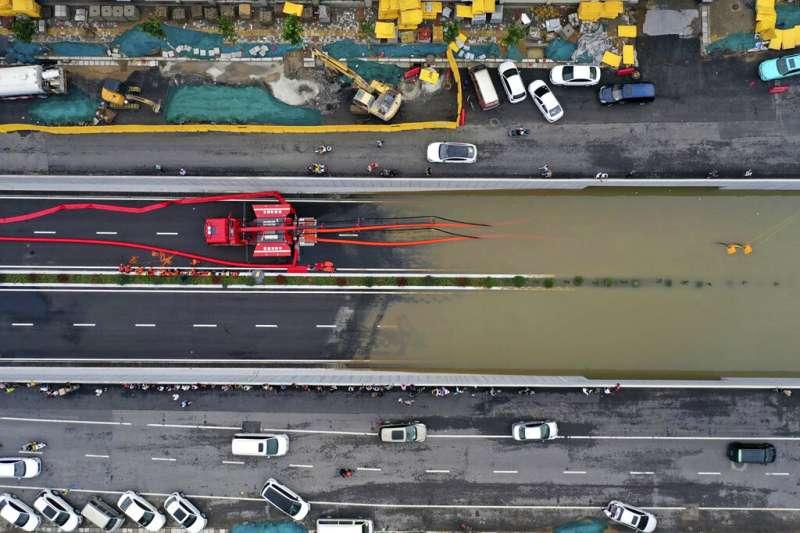 新華社7月21日發布的這張空拍照顯示,河南鄭州的消防隊員在大雨過後,正設法抽乾路面積水。(美聯社)