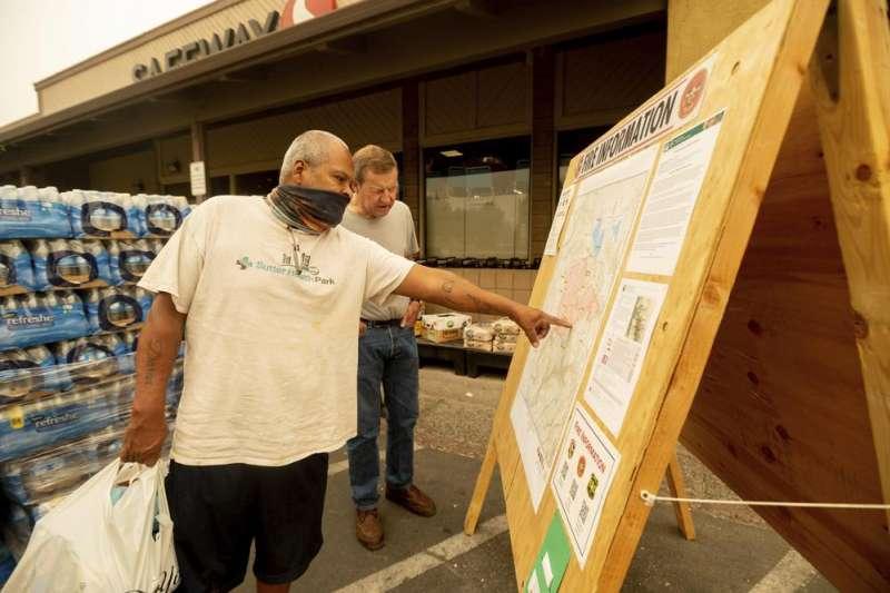 7月25日,美國加州昆西郡民眾正在看火災面積圖(美聯社)