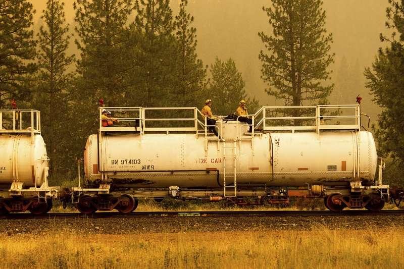7月24日,美國加州消防員搭著救火的火車(美聯社)