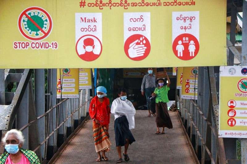 疫情下的緬甸仰光街頭,橫幅上寫著「消滅新冠疫情」。(美聯社)