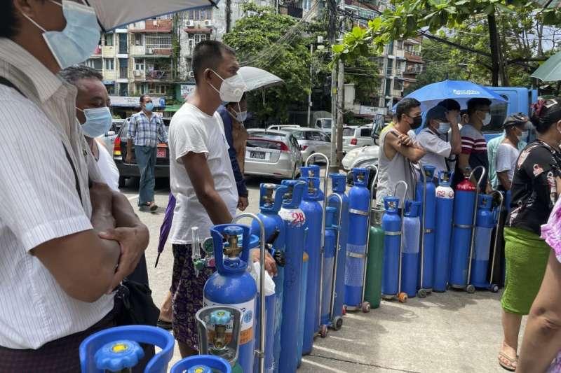 緬甸的新冠疫情近期相當嚴峻,7月11日,緬甸仰光民眾帶著氧氣罐在氧氣補給站外排隊(美聯社)