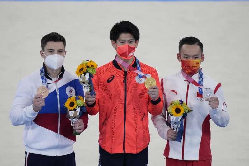 駐日代表謝長廷表示,「由日本選手橋本大輝(中)贏了中國的肖若騰(右)而拿到金牌,過程充滿戲劇化,我看體操比賽的經歷60年,以這次最精彩」。(美聯社)