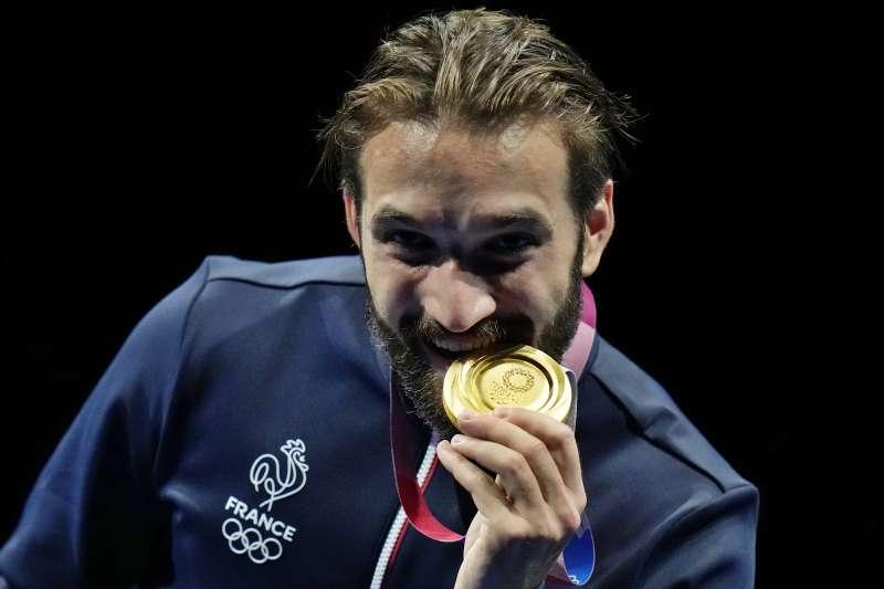 25日,2020東京奧運男子個人重劍比賽頒獎典禮上,法國選手坎農 (Romain Cannone) 咬著他的金牌。(AP)