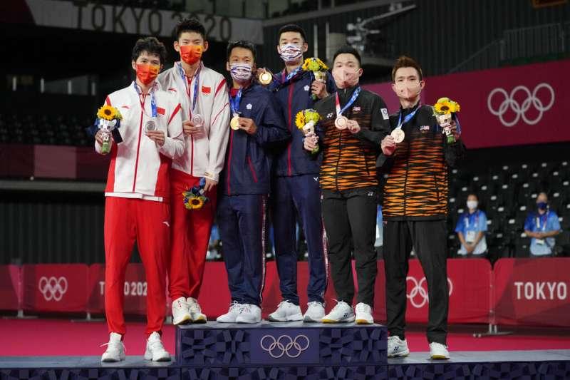 東京奧運羽球男雙的獎牌得主合照,我國最強組合王齊麟與李洋勇奪金牌。(美聯社)