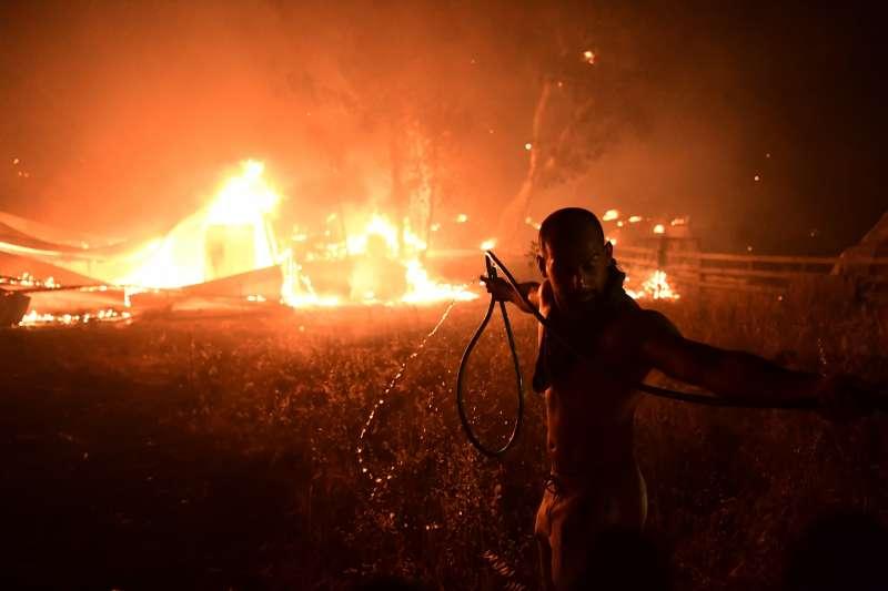 8月3日,希臘雅典北部Adames區,一名男子想用水管滅火(美聯社)
