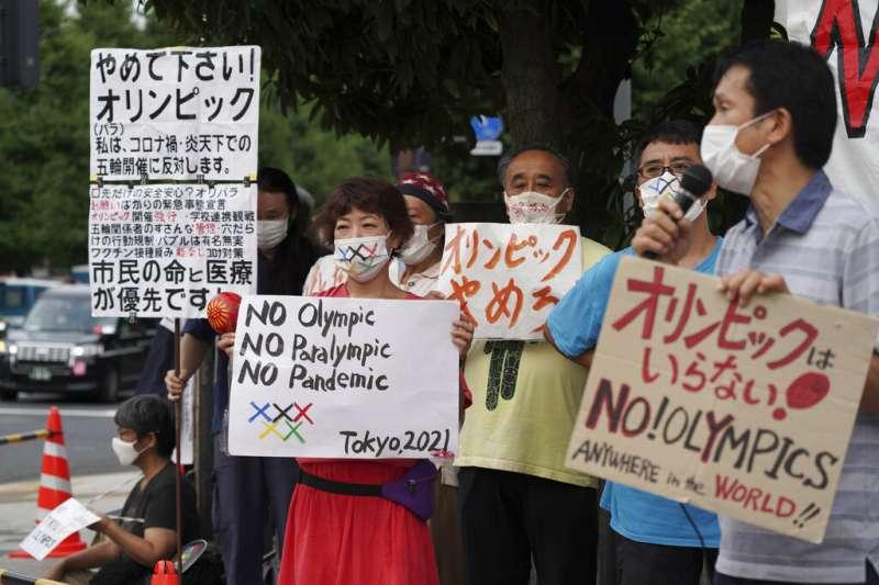 反對舉行東京奧運跟帕運的日本民眾,在總理大臣官邸附近舉牌抗議。(美聯社)