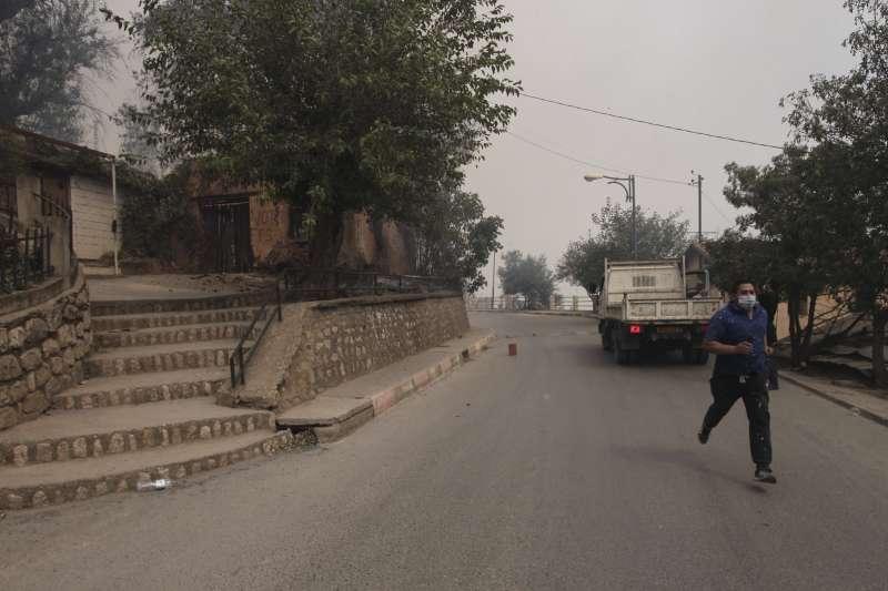 8月10日,阿爾及利亞提濟烏祖發生多起野火,附近村莊的一位居民正逃離家園(美聯社)