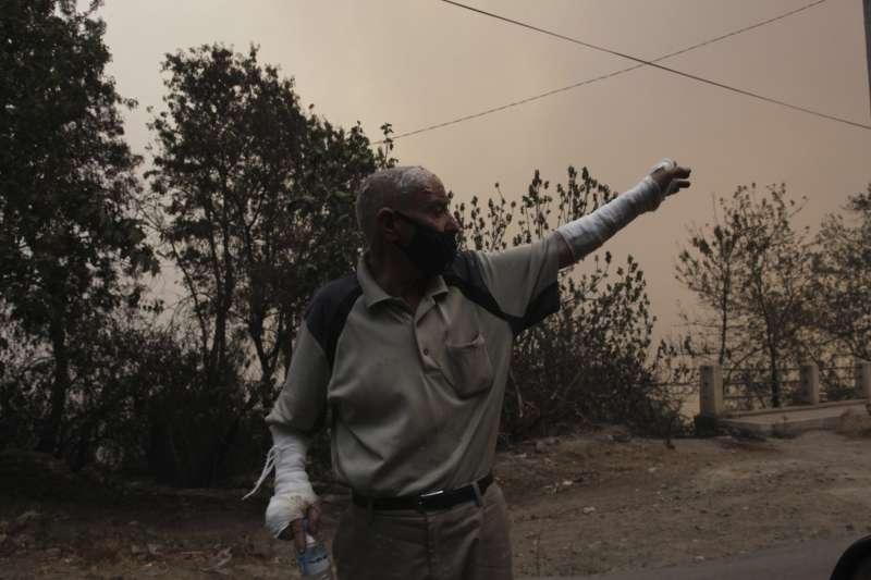 8月10日,阿爾及利亞提濟烏祖發生多起野火,附近村莊的一位居民逃離了家園(美聯社)