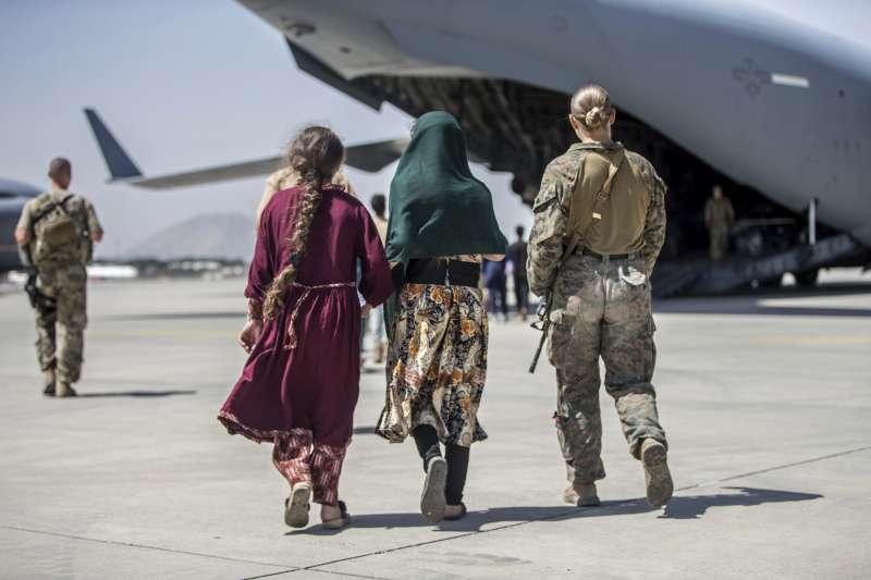 2021年8月24日,一名美軍陸戰隊24遠征隊的成員正在陪同準備撤離的阿富汗公民登機。(資料照,美聯社)