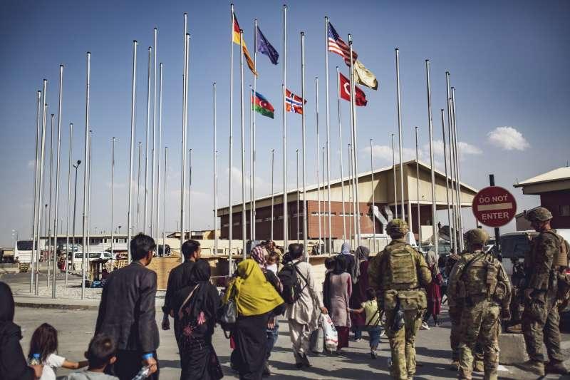 2021年8月24日,護衛喀布爾機場的美軍正在護送準備撤離的阿富汗公民進入機場。(美聯社)