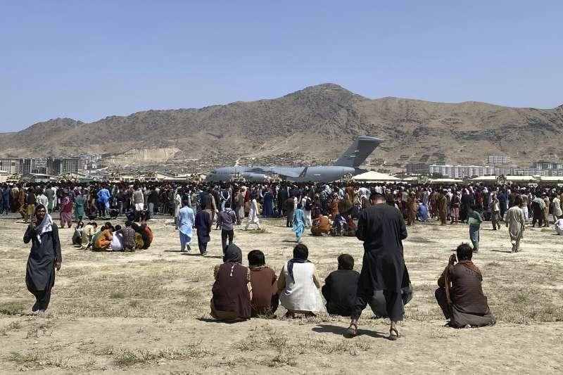 在喀布爾機場外圍遙望C-17的阿富汗人。(美聯社)