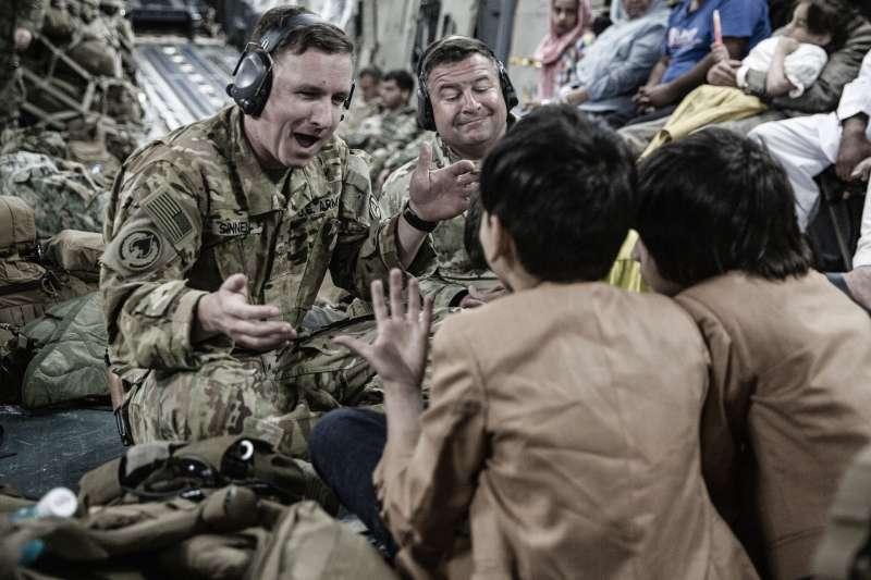 美軍與阿富汗兒童在撤離喀布爾的C-17上嬉戲。(美聯社)