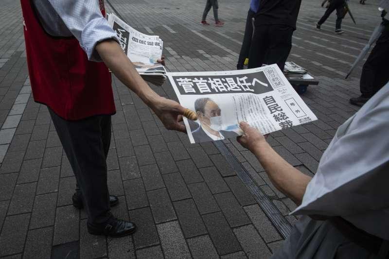2021年9月3日,菅義偉宣布不再競選連任自民黨總裁,日媒隨即在地鐵站發送號外。(美聯社)