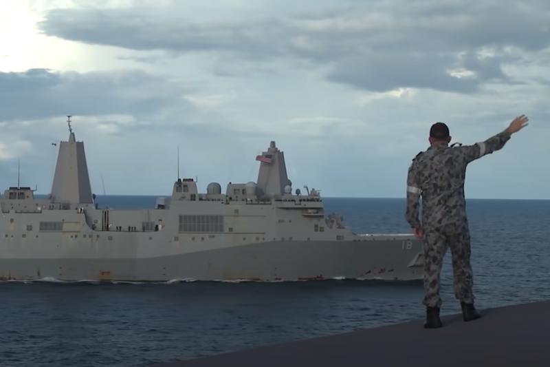 一名澳洲軍人向參與美澳聯合軍演的美軍軍艦揮手。(澳洲皇家海軍)