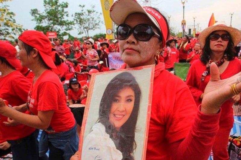 手持盈拉相片,力挺政府的紅衫軍於今年4月初集結於曼谷近郊。(美聯社)