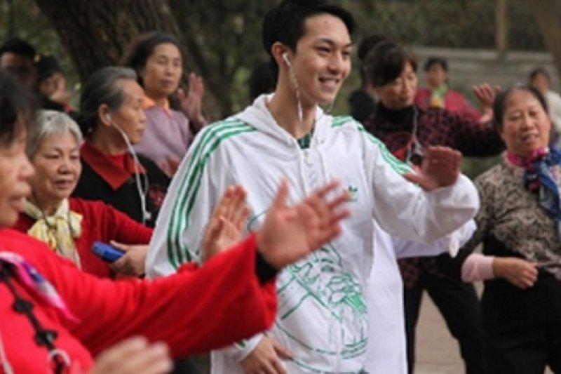 何乾梁(中立白衣者)在廣州天河公園推廣戴耳機「默跳」廣場舞。(圖片來源:取自網路)
